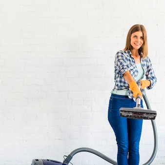 Smiling young woman holding vacuum cleaner in front of brick wall