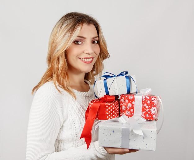 Улыбающаяся молодая женщина, держащая завернутые подарки