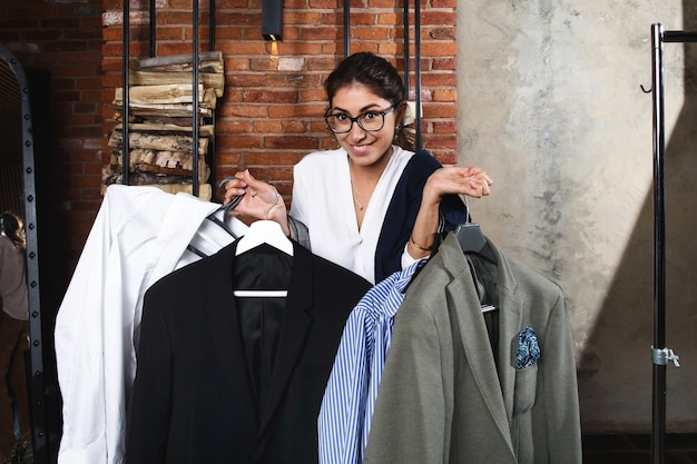 Smiling young woman holdning several hangers with man clothes in modern appartments interior