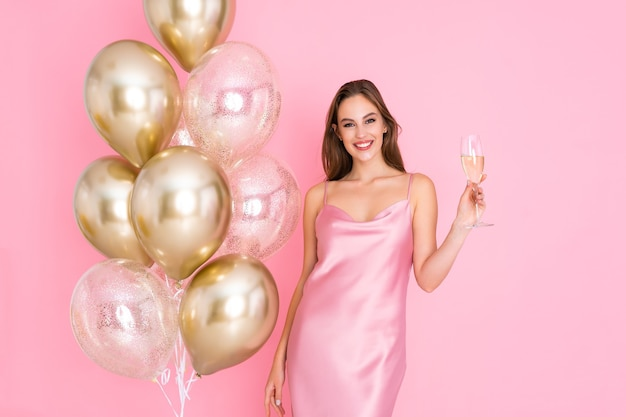 Smiling young woman holds glass of champagne stands near air balloons came to party celebration