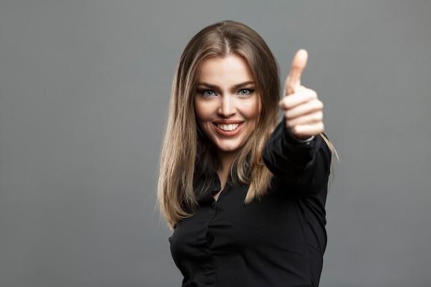 Улыбающаяся молодая женщина держит палец вверх. карский блондин в черной рубашке. успех, позитив и энергия. серый фон.