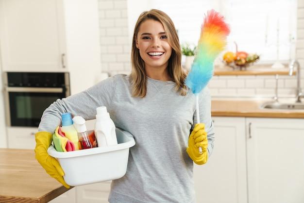 Улыбающаяся молодая женщина-домохозяйка в перчатках держит бутылки с моющим средством и красочную тряпку на современной кухне