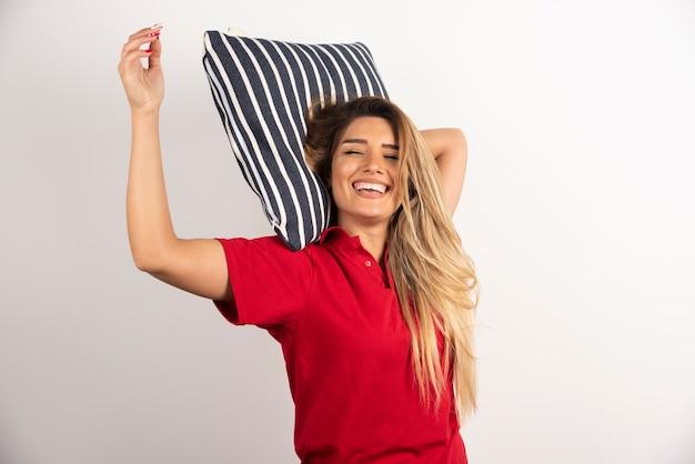 白い背景の上の枕を抱いて笑顔の若い女性。