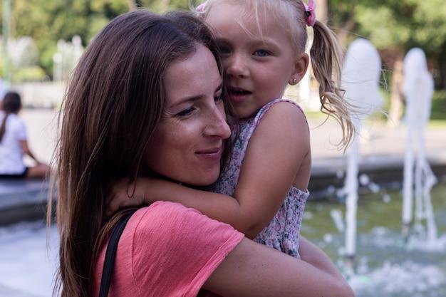 웃는 젊은 여자는 분수 근처 공원에서 어린 소녀를 안아줍니다.
