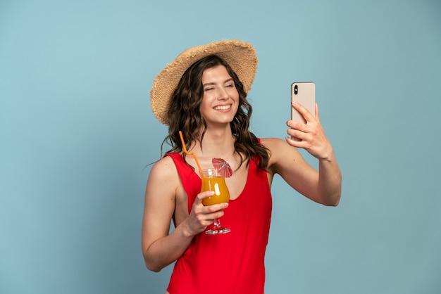 麦わら帽子をかぶった赤い水着とカクテルを片手に笑顔の若い女性が電話で自分撮りをします