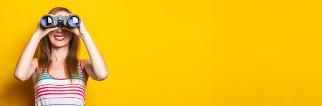 Улыбающаяся молодая женщина в полосатом платье, глядя в бинокль на желтом пространстве. баннер