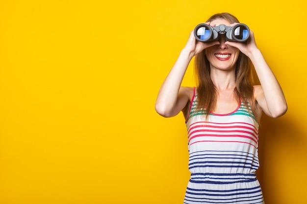 Улыбающаяся молодая женщина в полосатом платье смотрит в бинокль на желтом пространстве