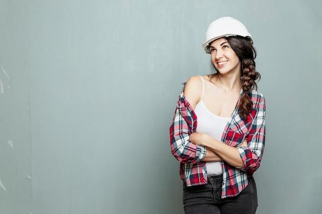 灰色の壁の背景に白い建設ヘルメットで若い女性の笑顔。ジーンズとチェック柄のシャツのブルネット。建設、改修、設計。テキスト用のスペース。