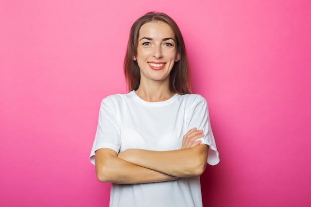 Улыбающаяся молодая женщина в белой футболке со скрещенными на груди руками на розовом