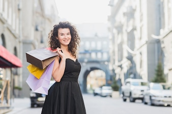 Smiling young woman in black dress holding shopping bags
