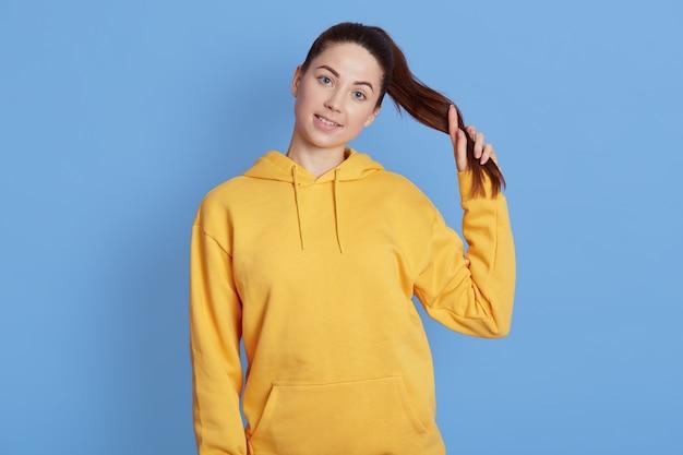 青い壁に孤立したポーズ、ポニーテールを保持し、魅力的な笑顔でカメラを見て、前向きな感情を表現するカジュアルな黄色のパーカーで若い女性を笑顔。