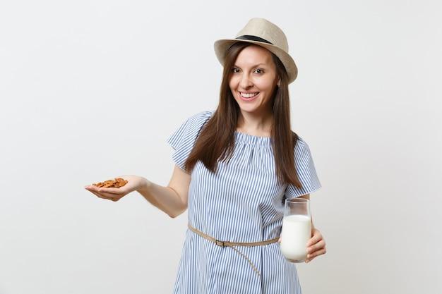 ドレスを着た若い女性の笑顔、帽子を手に持つガラスのアーモンドミルク、白い背景で隔離のアーモンドナッツ。適切な栄養、ビーガンベジタリアンドリンク、健康的なライフスタイル、ダイエットのコンセプト。コピースペース