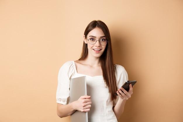 휴대 전화에 흥미로운 뉴스를 읽고, 노트북을 들고, 카메라에 행복 찾고, 베이지 색 배경에 서있는 안경에 젊은 여자를 웃고.