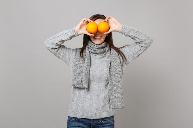 Улыбающаяся молодая женщина в сером шарфе свитера, покрывающего глаза апельсинами, изолированными на сером фоне в студии. здоровый образ жизни моды, искренние эмоции людей, концепция холодного сезона. копируйте пространство для копирования.