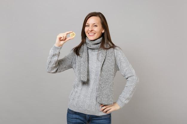 회색 스웨터를 입은 웃고 있는 젊은 여성, 스카프는 회색 벽 배경에 격리된 미래 통화인 비트코인을 들고 있습니다. 건강한 패션 라이프스타일, 사람들의 진심 어린 감정, 추운 계절 개념. 복사 공간을 비웃습니다.