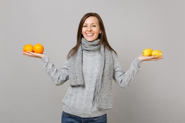 Улыбаясь молодая женщина в сером свитере, шарфе держать лимоны апельсины, изолированные на сером фоне студийный портрет. здоровый образ жизни моды, искренние эмоции людей, концепция холодного сезона. копируйте пространство для копирования.