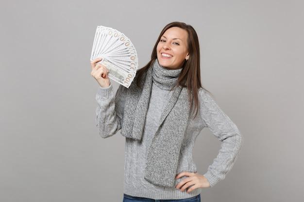 Улыбающаяся молодая женщина в сером свитере, шарфе держит много кучу долларов, банкноты, наличные деньги, изолированные на сером фоне, студийный портрет. эмоции людей здорового образа жизни моды, концепция холодного сезона.