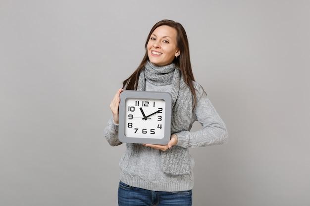 Улыбающаяся молодая женщина в сером свитере, шарфе удерживайте квадратные часы, изолированные на сером фоне, студийный портрет. здоровый образ жизни моды, искренние эмоции людей, концепция холодного сезона. копируйте пространство для копирования.