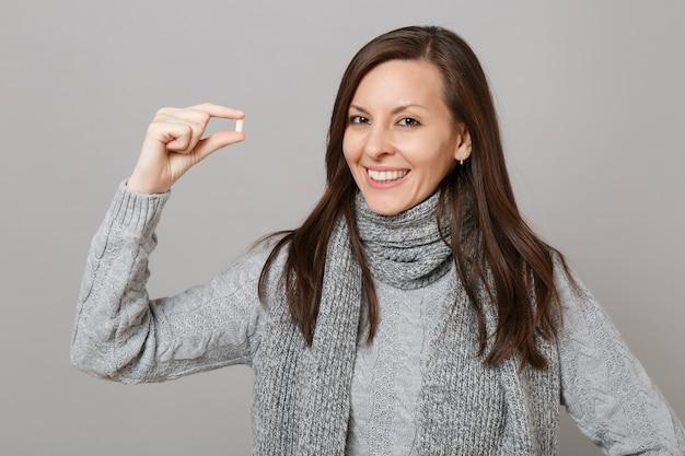 Улыбающаяся молодая женщина в сером свитере, шарфе, держащем таблетку лекарства, таблетку аспирина, изолированную на сером фоне. здоровый образ жизни, лечение больных, концепция холодного сезона. копируйте пространство для копирования.
