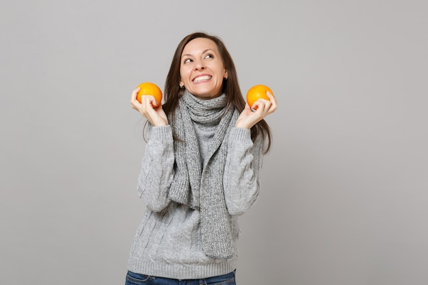 Улыбается молодая женщина в сером шарфе свитера, глядя вверх, держа апельсины, изолированные на сером фоне в студии. люди здорового образа жизни моды искренние эмоции, концепция холодного сезона. копируйте пространство для копирования.