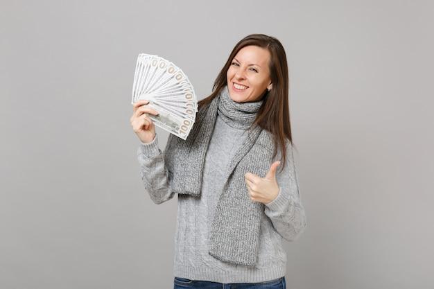 Улыбающаяся молодая женщина в сером свитере, шарфе, показывающем большой палец вверх, держит много кучу долларовых банкнот наличных денег, изолированных на сером фоне. эмоции людей здорового образа жизни моды, концепция холодного сезона.