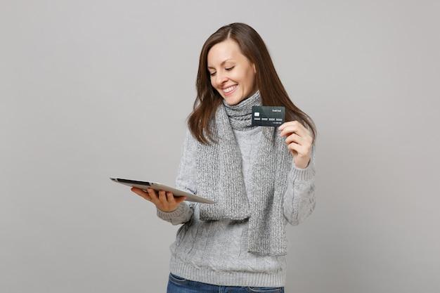 회색 스웨터를 입은 웃고 있는 젊은 여성, 태블릿 pc 컴퓨터를 사용하는 스카프, 회색 벽 배경에 격리된 신용 은행 카드를 들고 있습니다. 건강한 생활 방식, 온라인 치료 컨설팅, 추운 계절 개념.