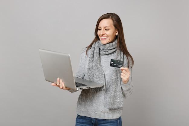 灰色のセーター、灰色の壁の背景に分離されたクレジット銀行カードを保持しているラップトップpcコンピューターで作業している若い女性の笑顔。健康的なライフスタイル、オンライン治療コンサルティング、寒い季節のコンセプト。