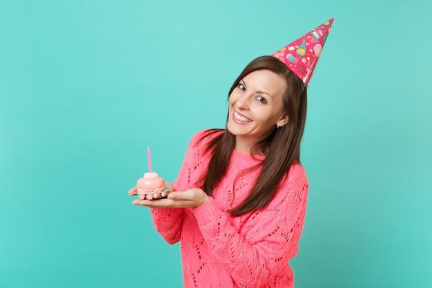 파란색 청록색 벽 배경 스튜디오 초상화에 격리된 촛불과 함께 손 케이크를 들고 니트 분홍색 스웨터와 생일 모자를 쓴 웃고 있는 젊은 여성. 사람들이 라이프 스타일 개념입니다. 복사 공간을 비웃습니다.