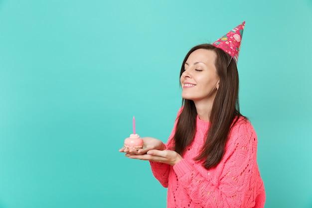 분홍색 스웨터를 입은 웃고 있는 젊은 여성, 눈을 감고 생일 모자를 들고 파란색 벽 배경 스튜디오 초상화에 촛불을 들고 손으로 케이크를 들고 있습니다. 사람들이 라이프 스타일 개념입니다. 복사 공간을 비웃습니다.