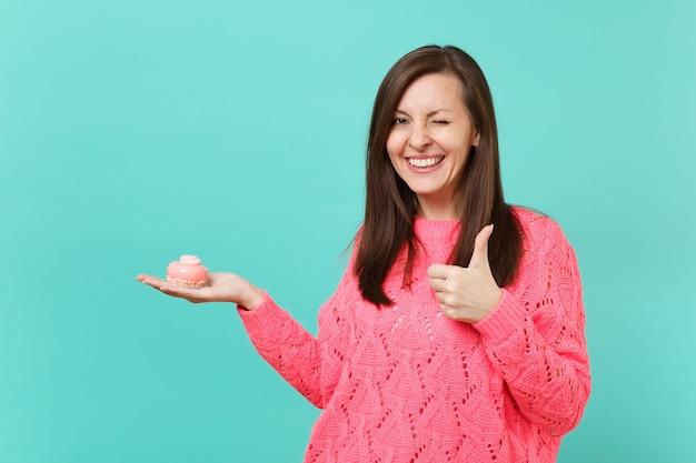 Улыбающаяся молодая женщина в вязаном розовом свитере мигает, показывая большой палец вверх, держа в руке торт, изолированный на синем фоне бирюзовой стены студийный портрет. концепция образа жизни людей. копируйте пространство для копирования.