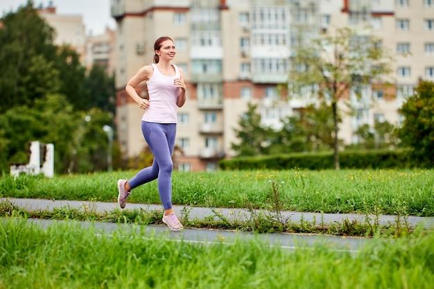Улыбающаяся молодая женщина в леггинсах бежит в общественном парке