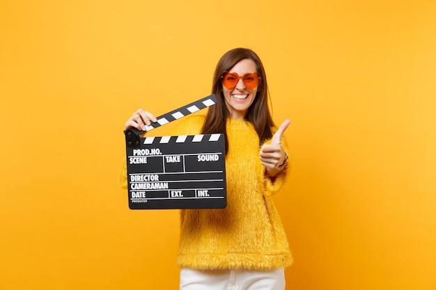 親指を上に表示し、黄色の背景で隔離のカチンコを作る古典的な黒いフィルムを保持しているオレンジ色のハートの眼鏡で若い女性を笑顔。人々は誠実な感情、ライフスタイル。広告エリア。