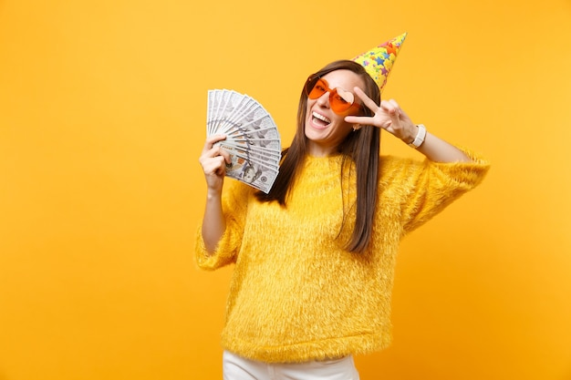 Улыбающаяся молодая женщина в оранжевых очках в форме сердца, шляпа на день рождения, показывающая знак победы, празднует, держа пачку долларов наличными деньгами, изолированными на желтом фоне. люди искренние эмоции, образ жизни.