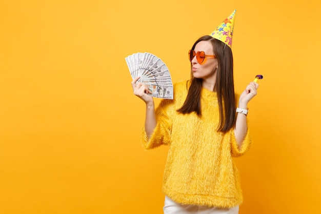 Улыбающаяся молодая женщина в оранжевых очках сердца, шляпа дня рождения с игральной трубой, глядя на пачку много долларов, празднование наличных денег на желтом фоне. люди искренние эмоции, образ жизни.