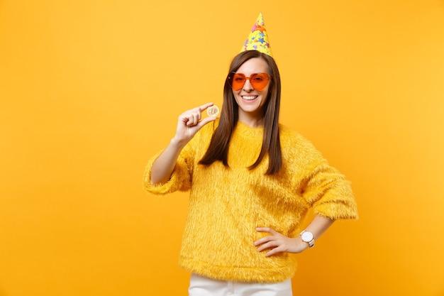 주황색 하트 안경을 쓴 웃는 젊은 여성, 비트코인을 들고 있는 생일 파티 모자, 황금색 금속 동전, 노란색 배경에 격리된 미래 통화. 사람들은 진심 어린 감정, 라이프 스타일 개념입니다.