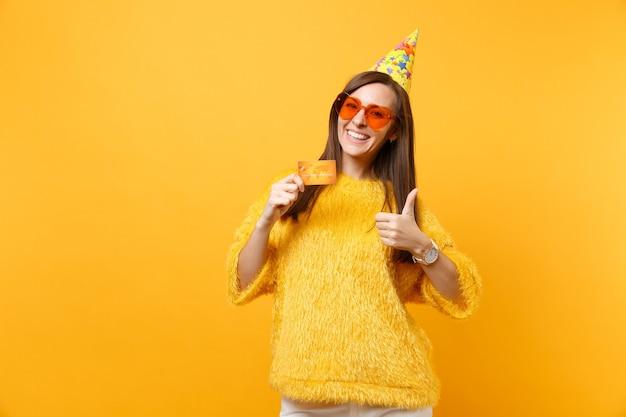 Улыбающаяся молодая женщина в оранжевых очках сердца, шляпа вечеринки по случаю дня рождения, показывая большой палец вверх, держа кредитную карту, наслаждаясь праздником, празднуя изолированное на желтом фоне. люди искренние эмоции, образ жизни.