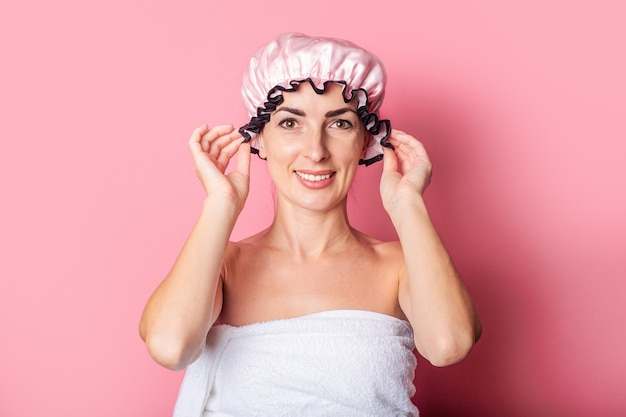 Улыбается молодая женщина в розовой шапочке для душа на розовом фоне.