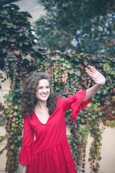 Улыбающаяся молодая женщина в красном платье