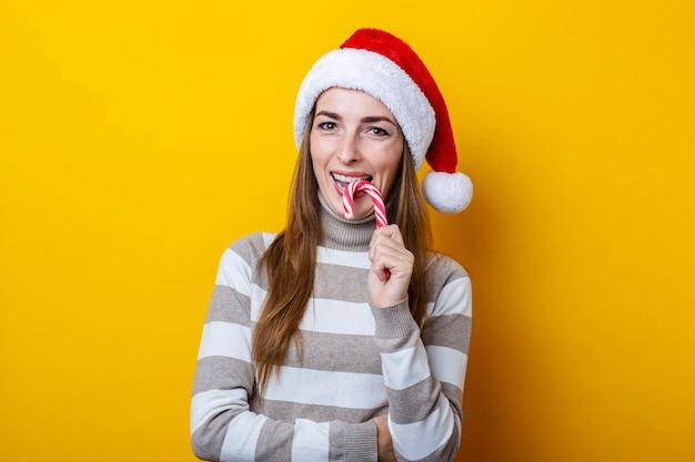 노란색 배경 위에 크리스마스 사탕을 먹고 산타 클로스 모자에 웃는 젊은 여자.