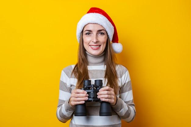 노란색 배경에 쌍안경으로 산타 클로스 모자에 웃는 젊은 여자.