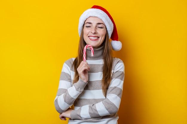 노란색 배경에 크리스마스 사탕과 눈을 감고 산타 클로스 모자에 웃는 젊은 여자.