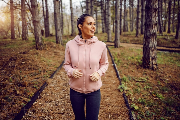 森の中で実行しているスポーツウェアの若い女性の笑みを浮かべてください。健康的な生活様式。自然のコンセプトで実行されています。