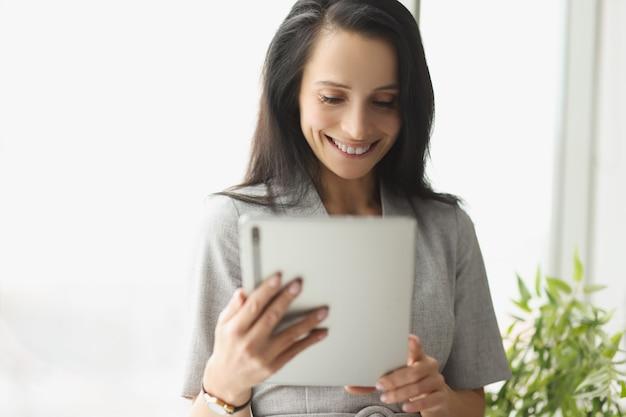 デジタルタブレットを保持しているスーツの若い女性の笑顔