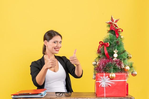 黄色のオフィスで飾られたクリスマスツリーの近くでokジェスチャーを作るスーツを着た若い女性の笑顔