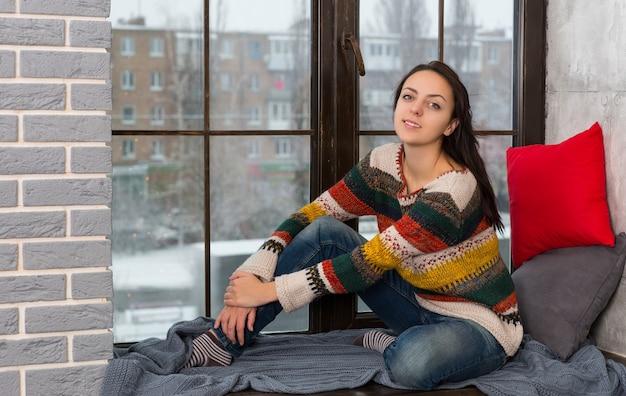 窓辺に座ってカメラを見ている暖かいニットセーターで若い女性の笑顔