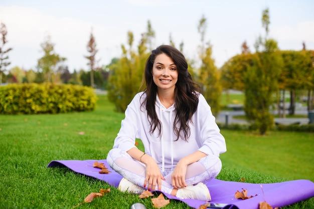 白いレギンス、パーカー、スニーカーで笑顔の若い女性は、秋の都市公園の背景で足を組んでスポーツマットに座っています。
