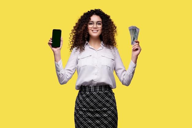 흰 셔츠에 웃는 젊은여자가 휴대 전화를 보유 하 고 돈을 원. 여성은 온라인 카지노에서 활약합니다.