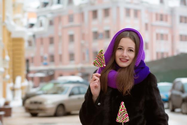 通りでおいしいカラフルなキャンディーでポーズをとって冬の服を着て若い女性の笑顔