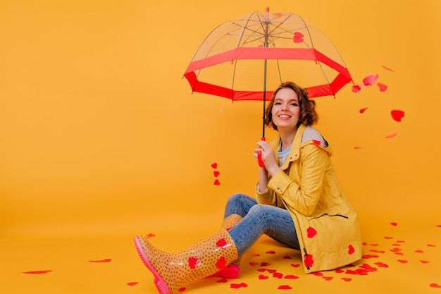 壁に赤いハートでポーズをとって黄色のコートを着た若い女性の笑顔。バレンタインデーを祝う、パラソルを持ったゴージャスな女の子。