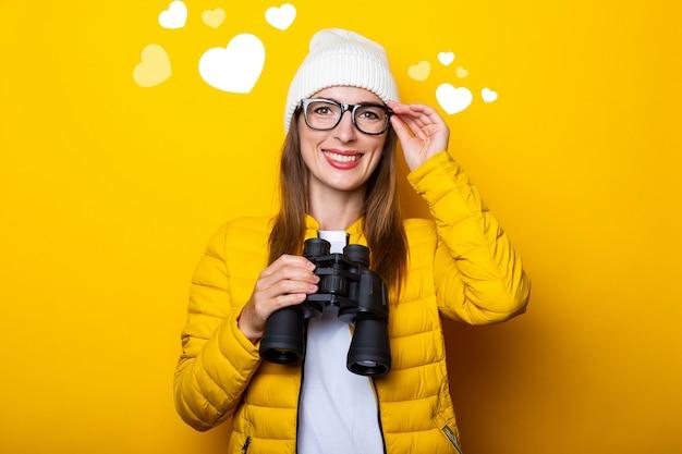 Улыбается молодая женщина в желтой куртке, держа бинокль на желтой стене.
